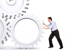 business man pushing a cogwheel to make it work (photo: )